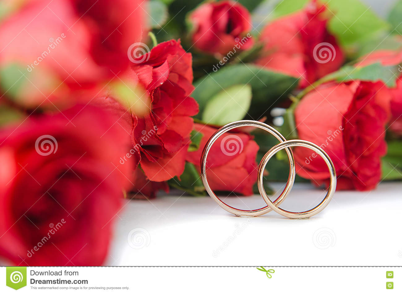 The wedding rings and flowers on white background