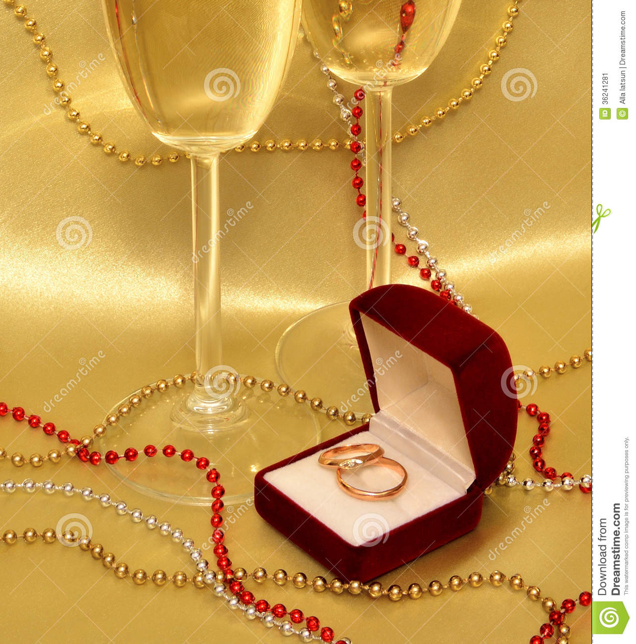 Wedding Rings And Glasses With Sparkling Wine On A Golden