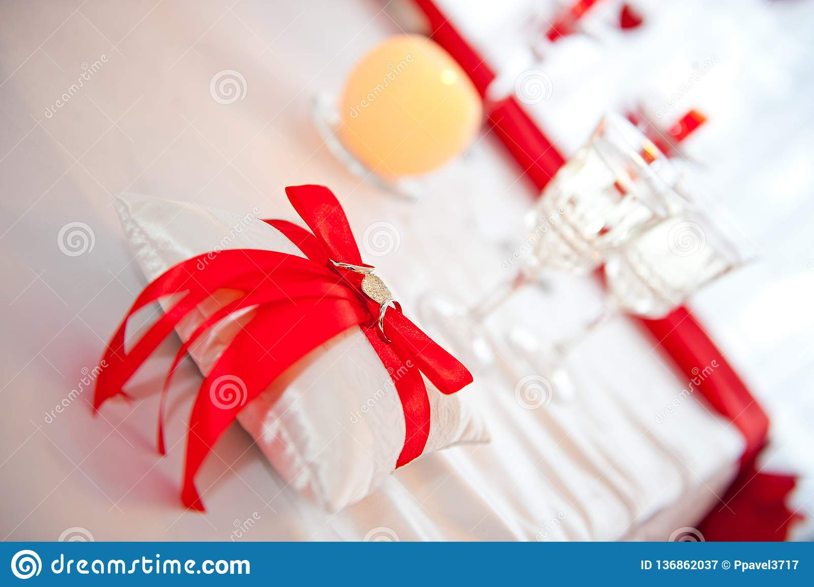 Wedding rings tied with a red ribbon with a heart on a pad shot against the background of two glasses of champagne