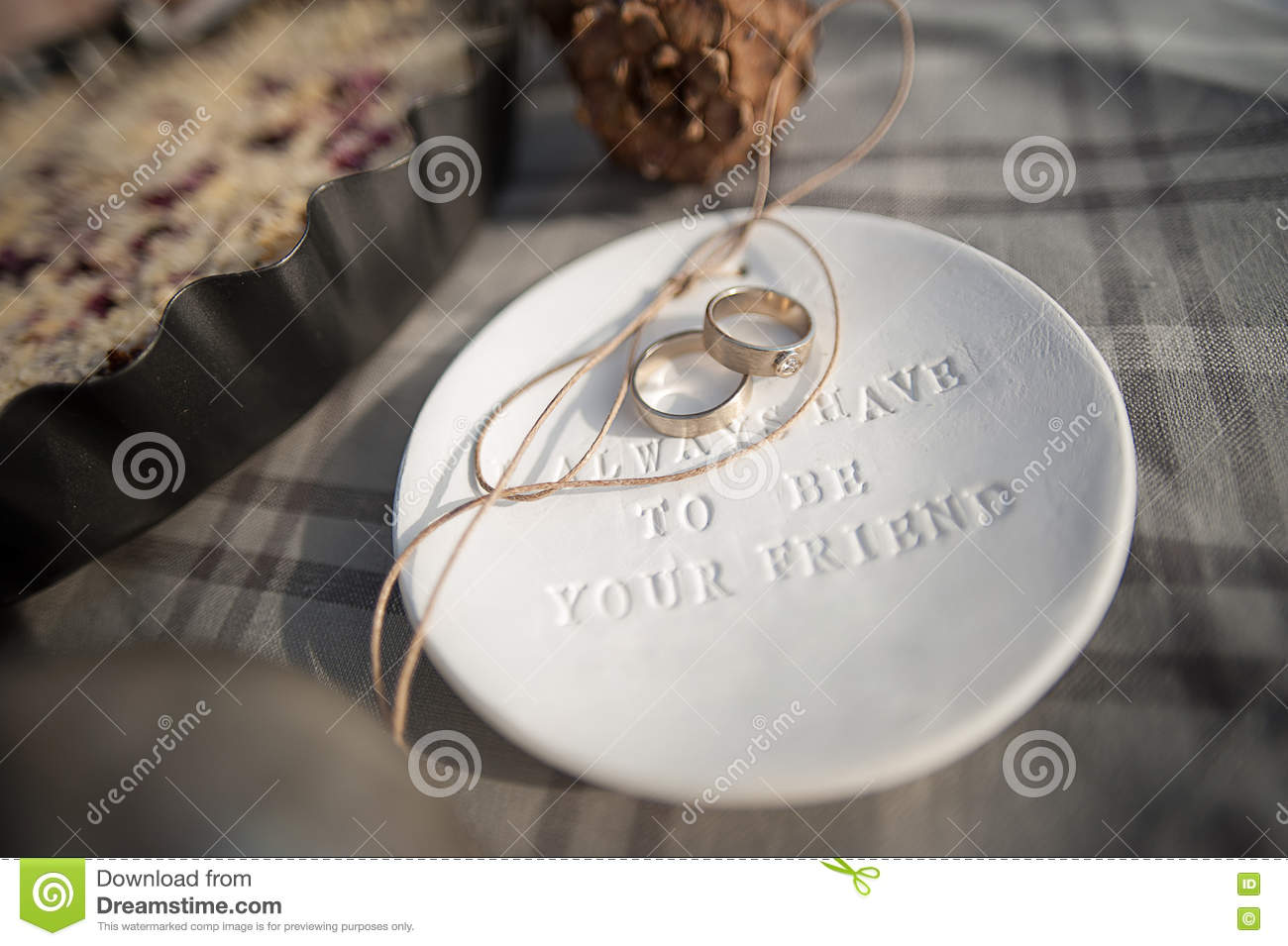 Wedding rings in white gold, clay saucer with the word always have to be your friend
