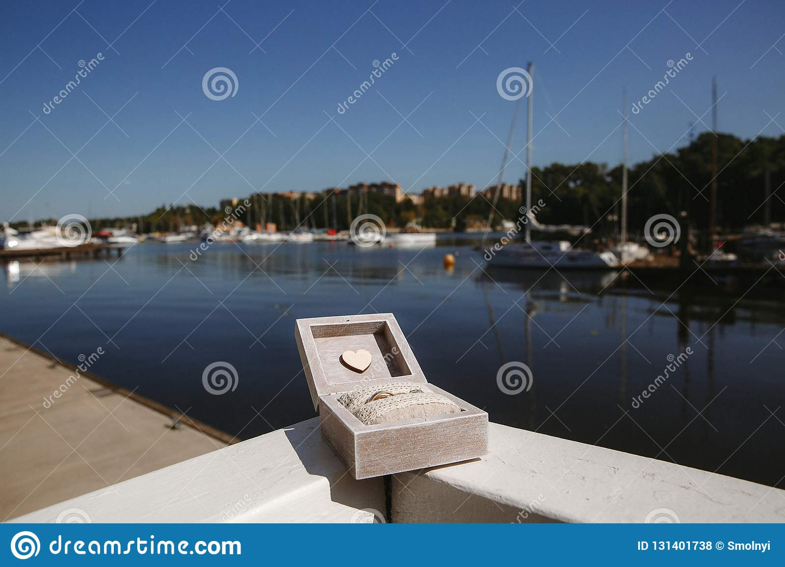 Wedding rings in a wooden box on the background of white yachts in a yacht club