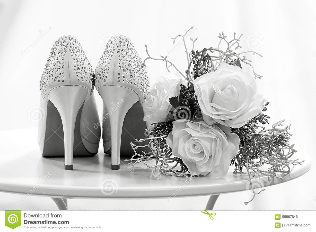 Wedding Shoes And Flowers On A Table Black And White Stock Photo