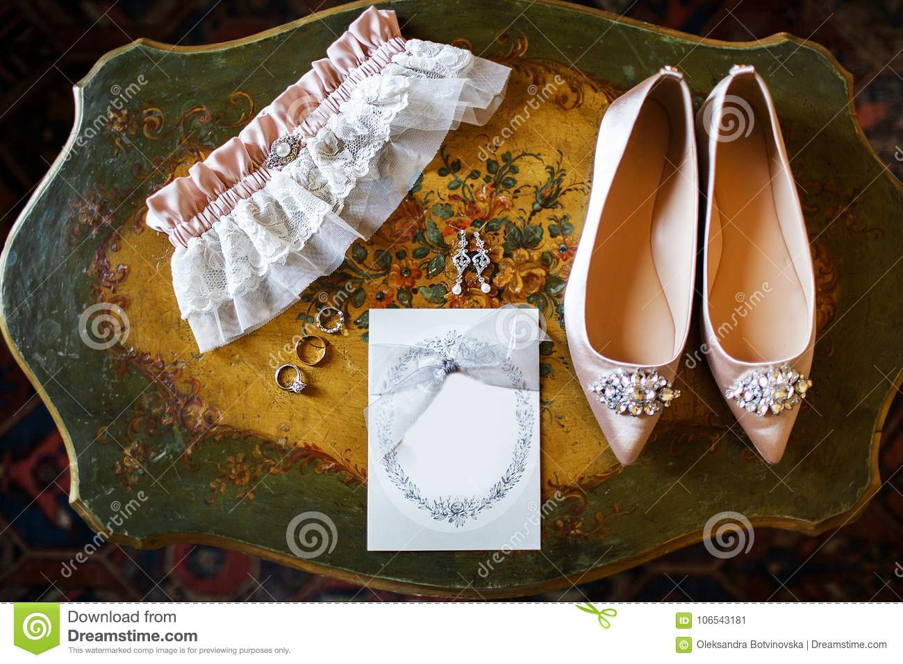 Wedding shoes on the vintage table, bridal garter and rings