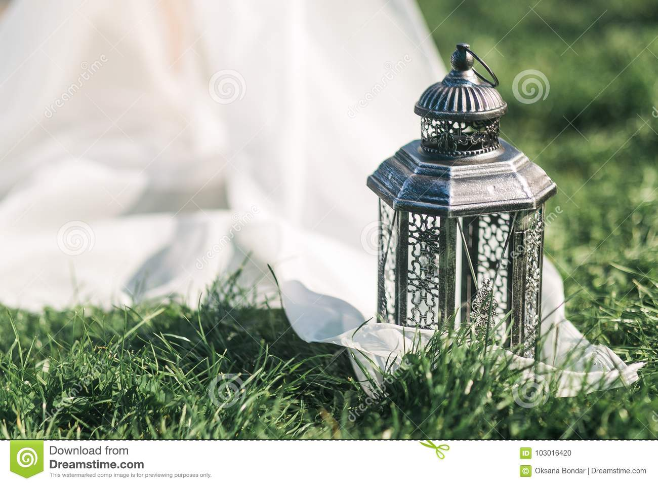 Wedding still life black lantern on grass and white tule in rustic style.