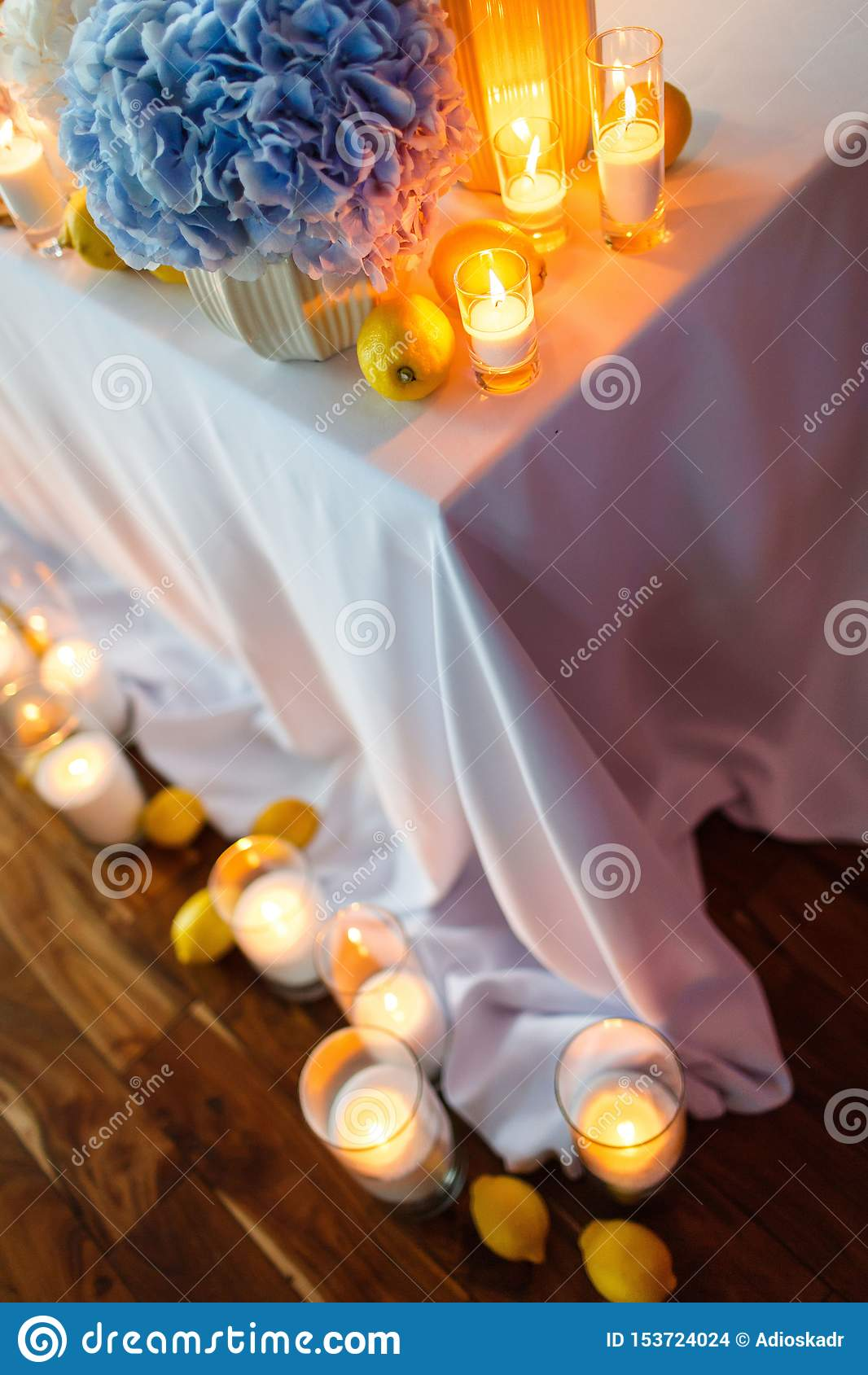 Wedding table decoration with candles and blue flowers