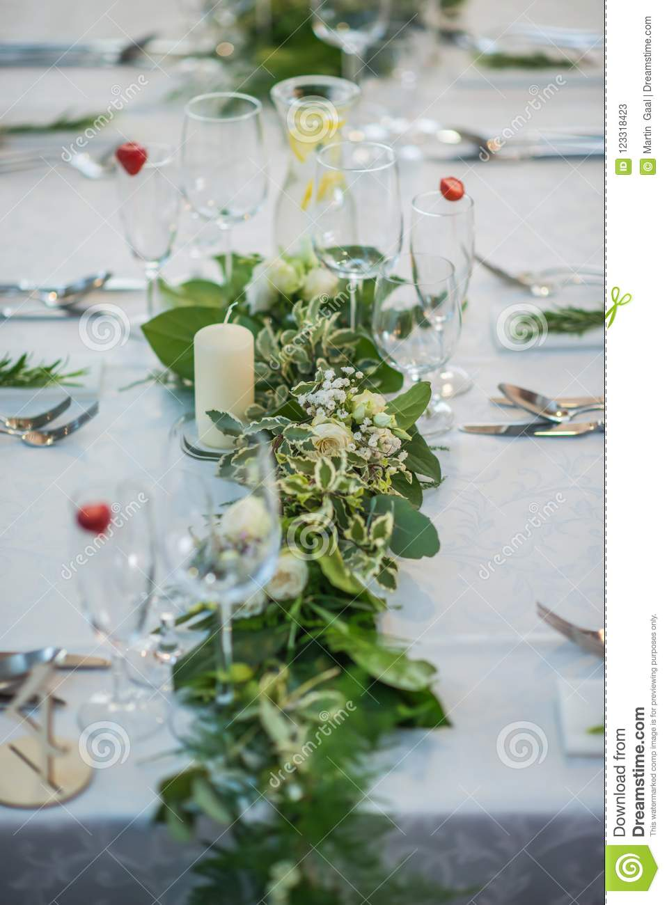Wedding table with exclusive floral arrangement prepared for reception, wedding or event centerpiece in greenery style