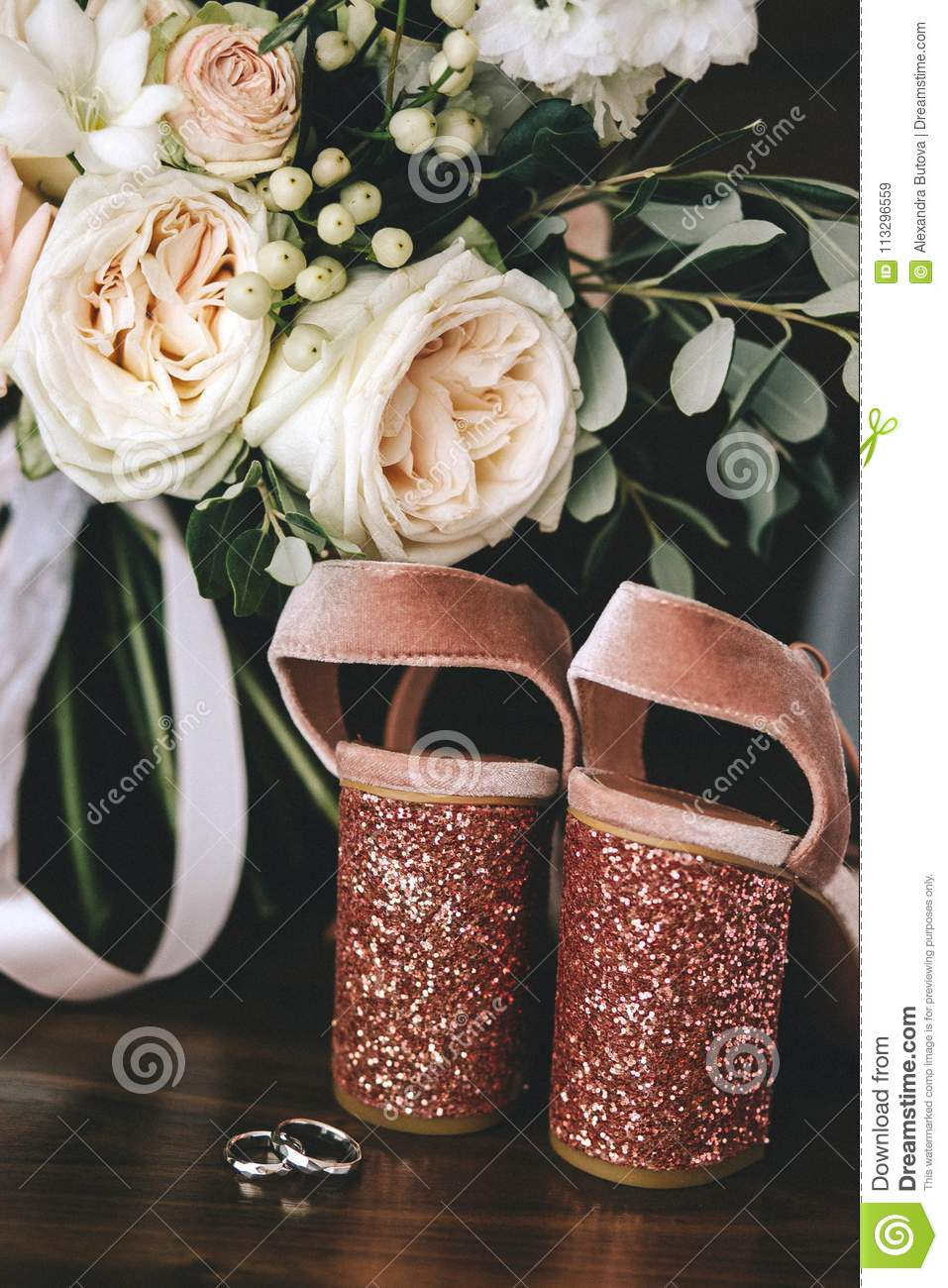 Wedding velvet pink shoes with shiny beautiful heels with gold wedding rings beside a bouquet of white roses, eucalyptus on a dark