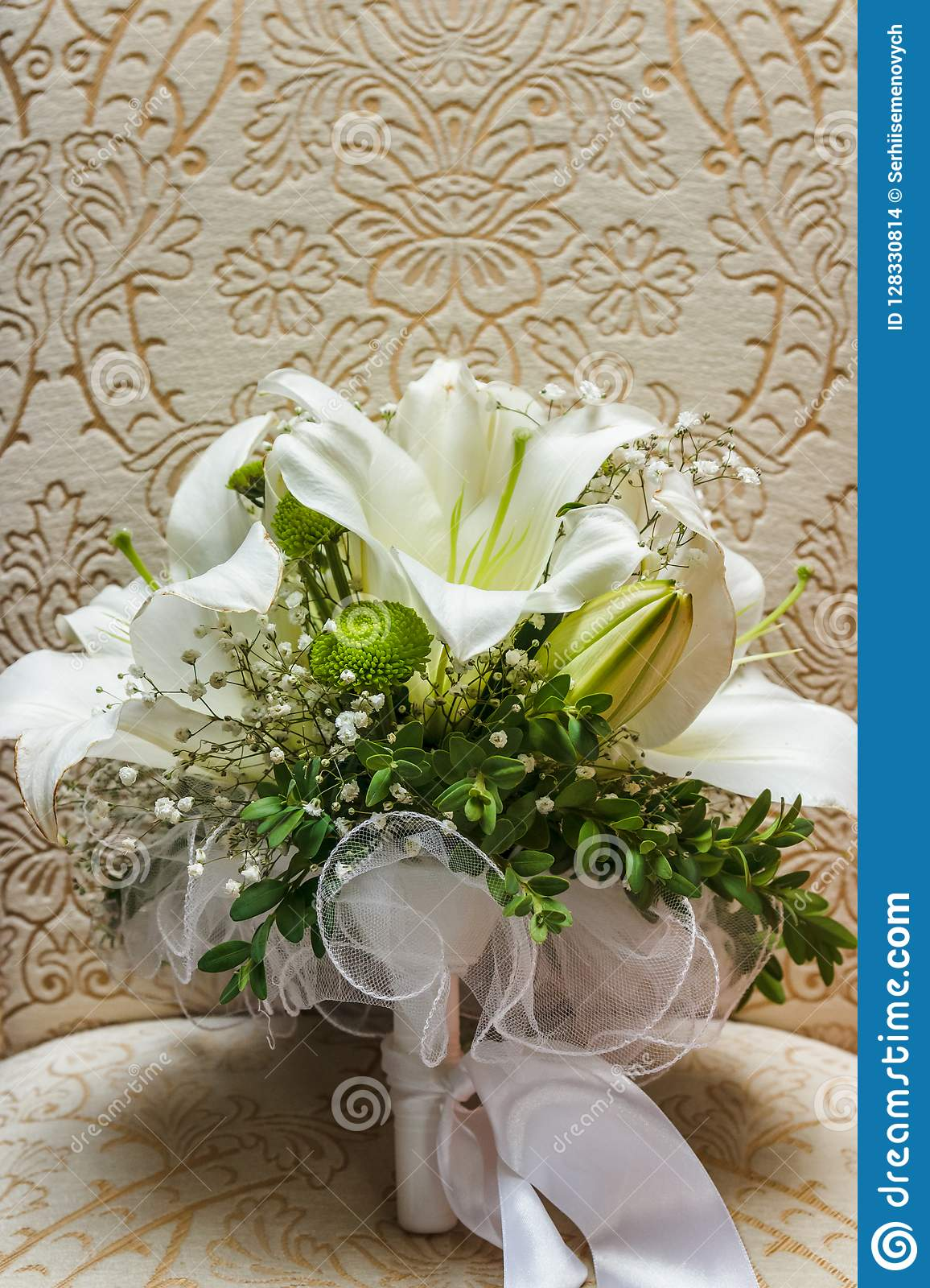 Wedding white bride shoes with a bouquet of white roses and other flowers, wedding rings on a stool