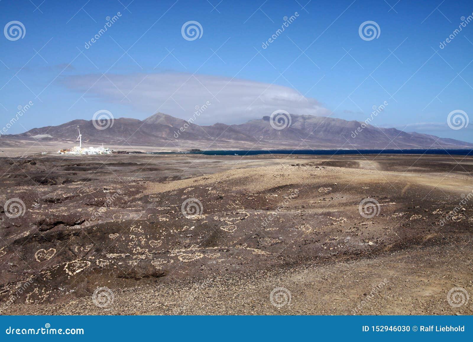 Weergeven op kleine witte dorp, bergketen en vlek van blauwe oceaan over eindeloos onvruchtbaar land, Fuerteventura, Canarische E