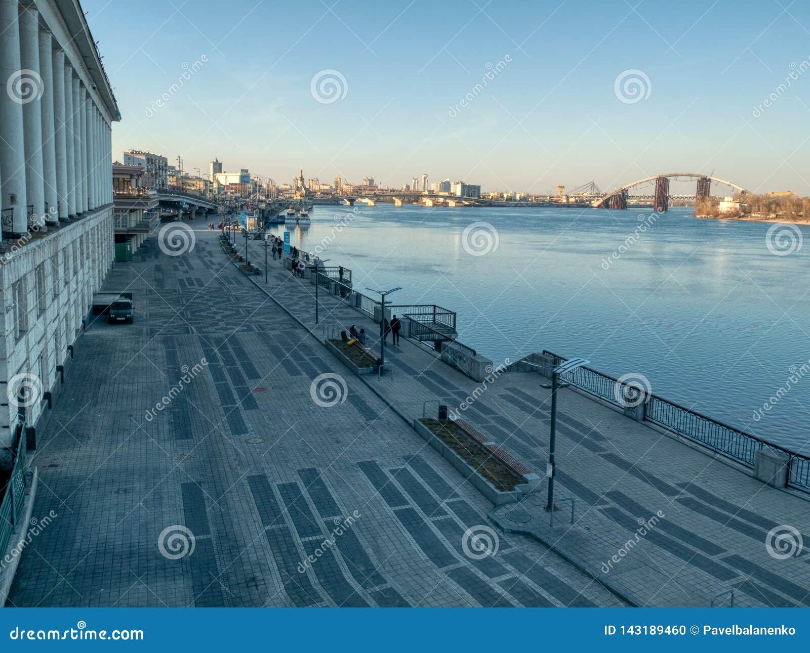 Weergeven op oude gesloten Rivierpost in Kiev en mensen die op dijk van Dnipro-rivier lopen