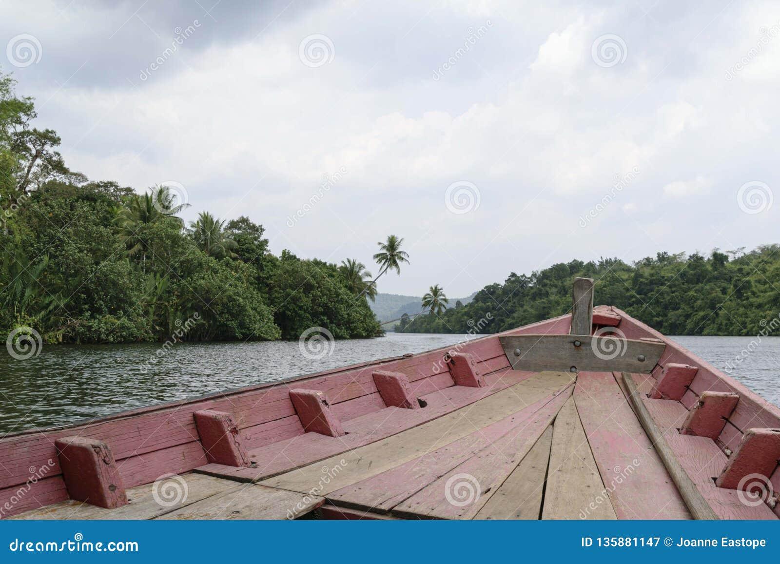 Weergeven over de boeg van een goed gebruikte houten boot die op Rivier Kong en knipsel door de dichte wildernis reizen