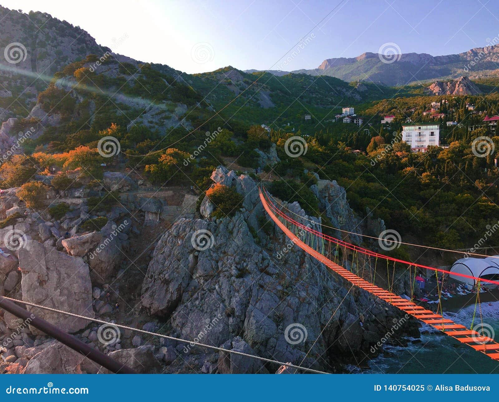 Weergeven van brug van de opschortings de rode kabel op bergachtergrond