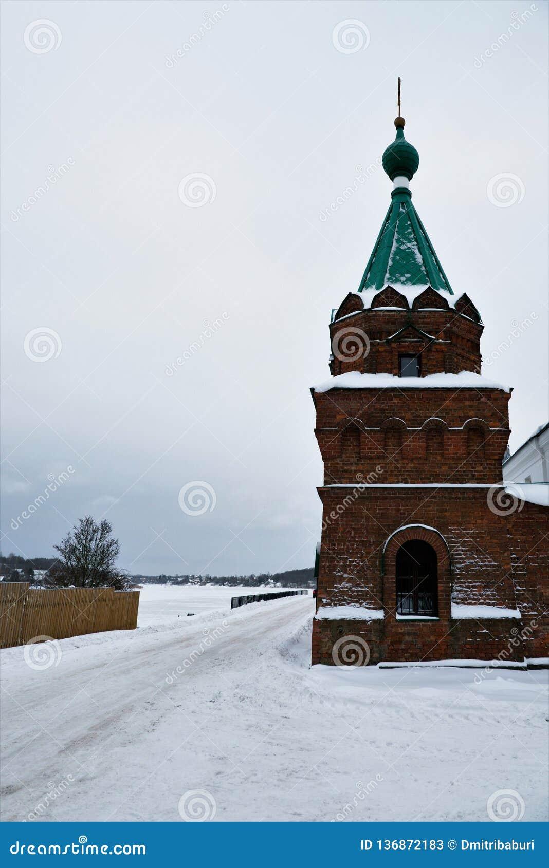 Weergeven van de hoektoren van het klooster van omheiningsNikolsky en de Volkhov-Rivier in de winter