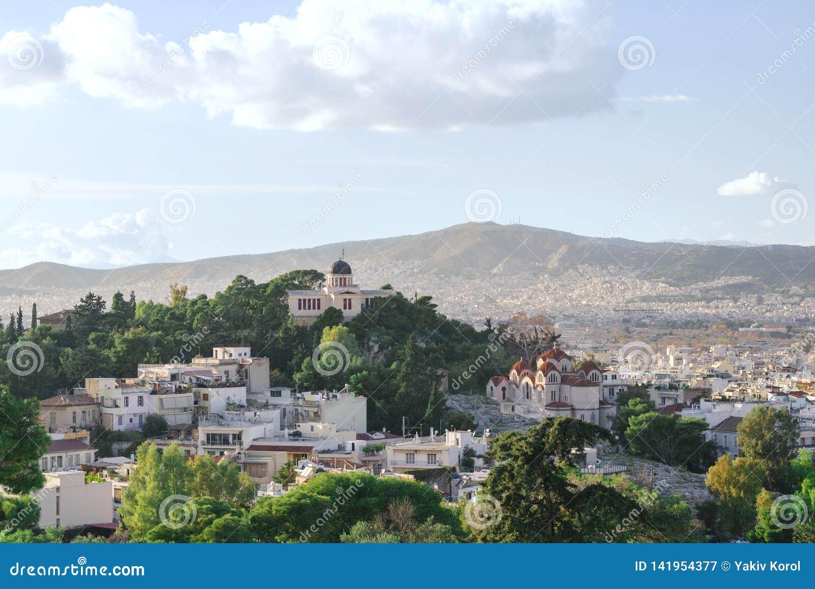 Weergeven van de stad van Athene, de kerk en de bergen van de Akropolis Groene bomen en blauwe hemel