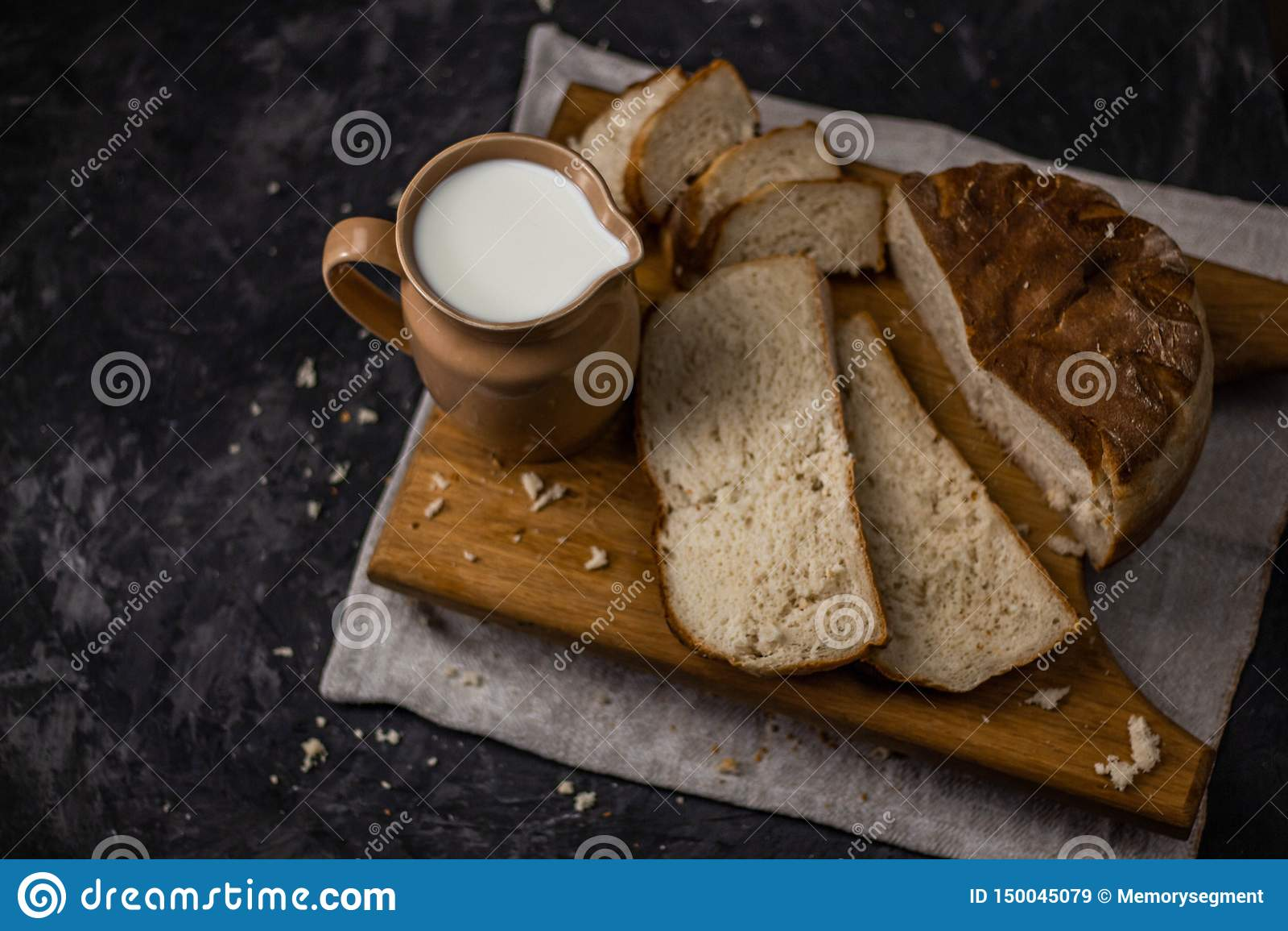 Weergeven van een kruik melk en eigengemaakt vers gebakken wit brood op een zwarte achtergrond