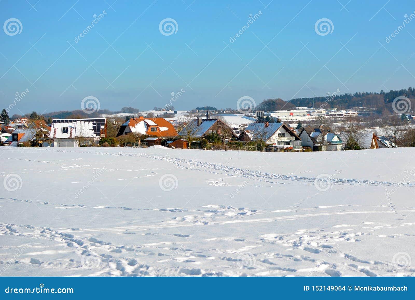 Weergeven van kleine landelijke die stad in Odenwald in Duitsland met opheldering in sneeuw tijdens de winter wordt behandeld