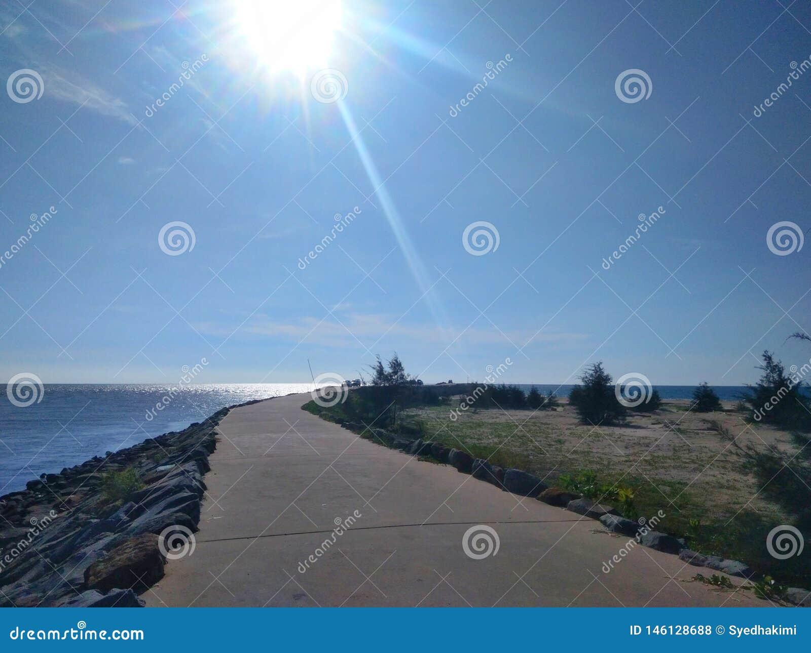 Weg aan pijler en oceaanmening met de steen van de golfbreker - beeld