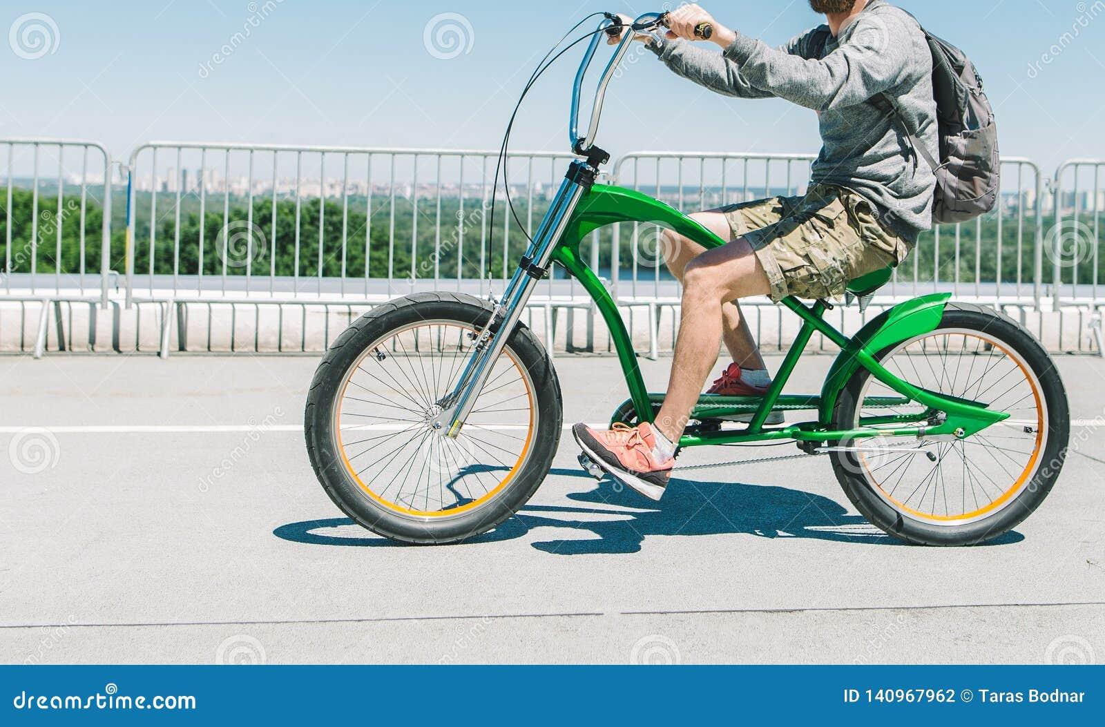 Weg auf einem stilvollen grünen Fahrrad um die Stadt Ein Radfahrer in der zufälligen Kleidung reitet ein Stadtfahrrad auf Asphalt