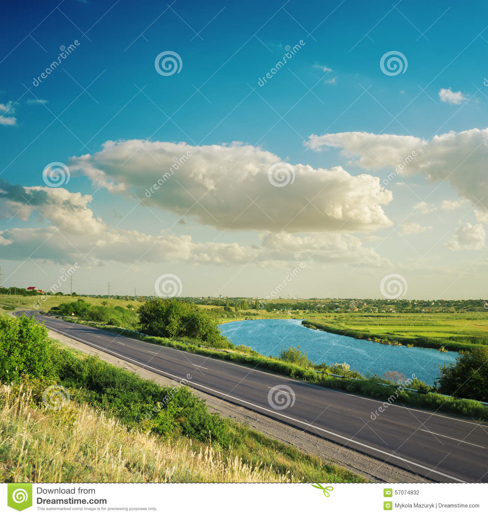 Weg dichtbij rivier onder wolken in blauwe hemel