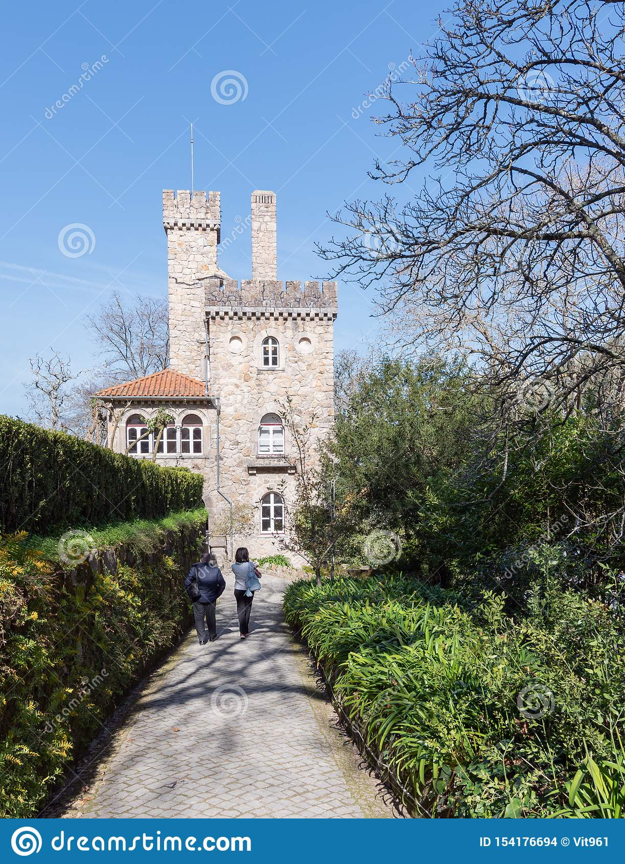 Weg mit zwei Leuten entlang dem Weg entlang der grünen Gasse auf dem Hintergrund eines alten Schlosses