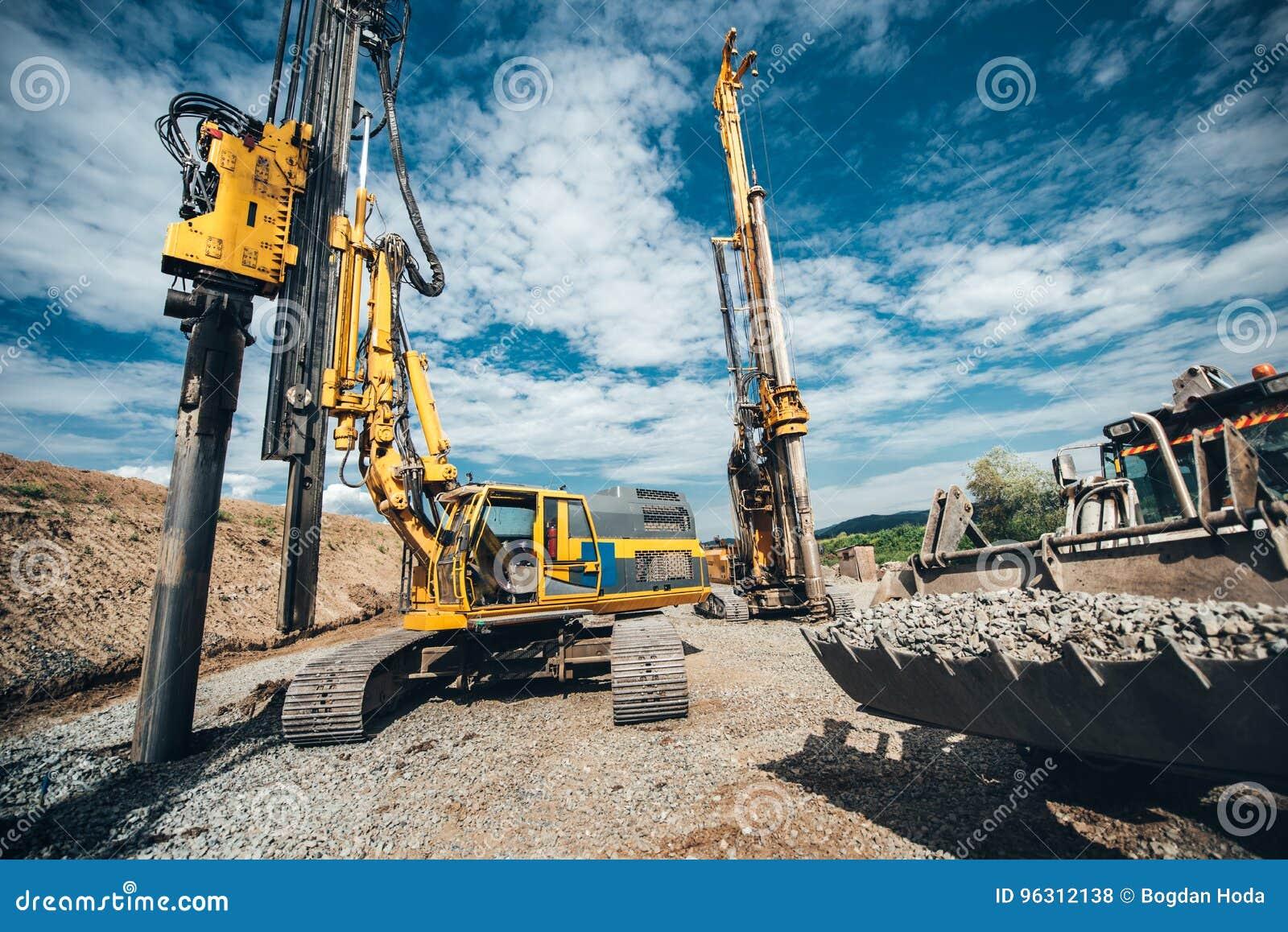 Wegbouw met op zwaar werk berekende machines Twee Roterende boren, bulldozer en graafwerktuig het werken