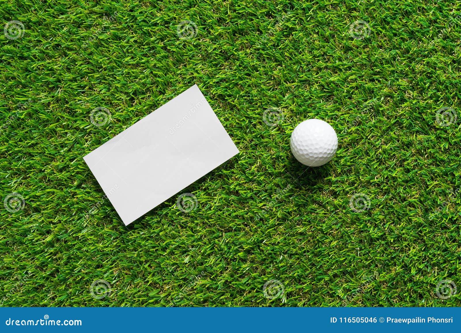 Weißbuchhintergrund und -Golfball auf grünem Gras des Golfplatzes
