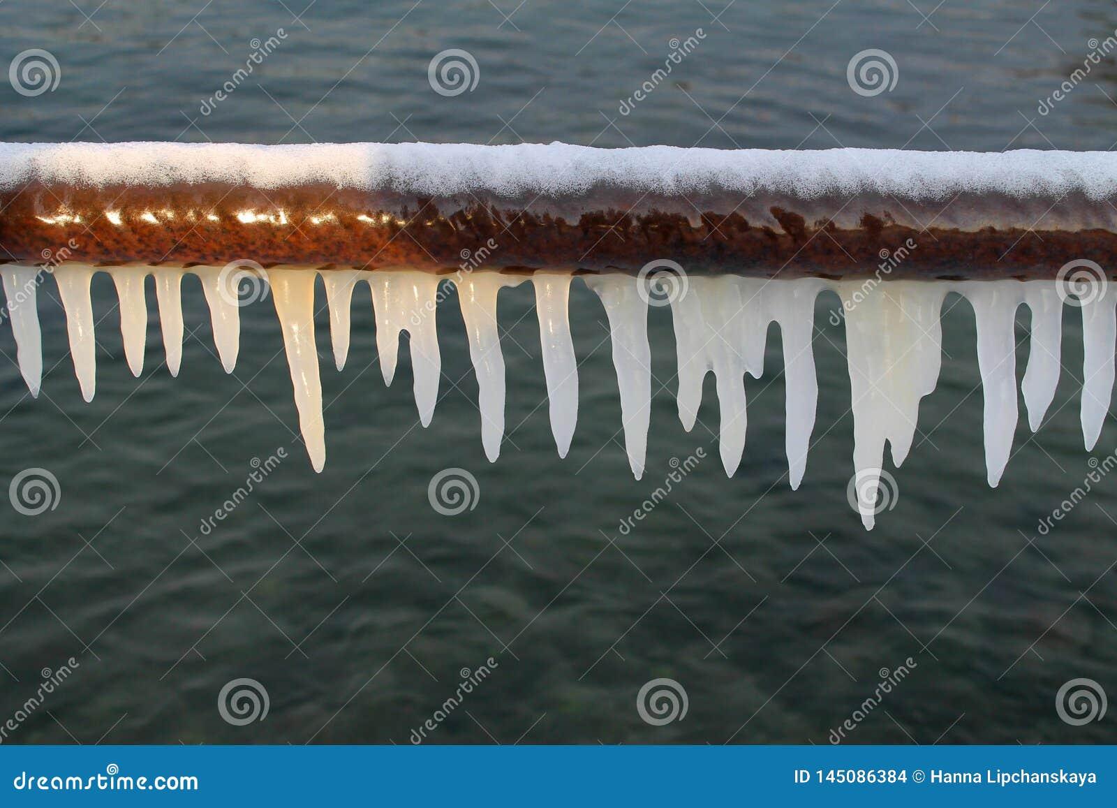 Weiße Eiszapfen auf einem Rohr