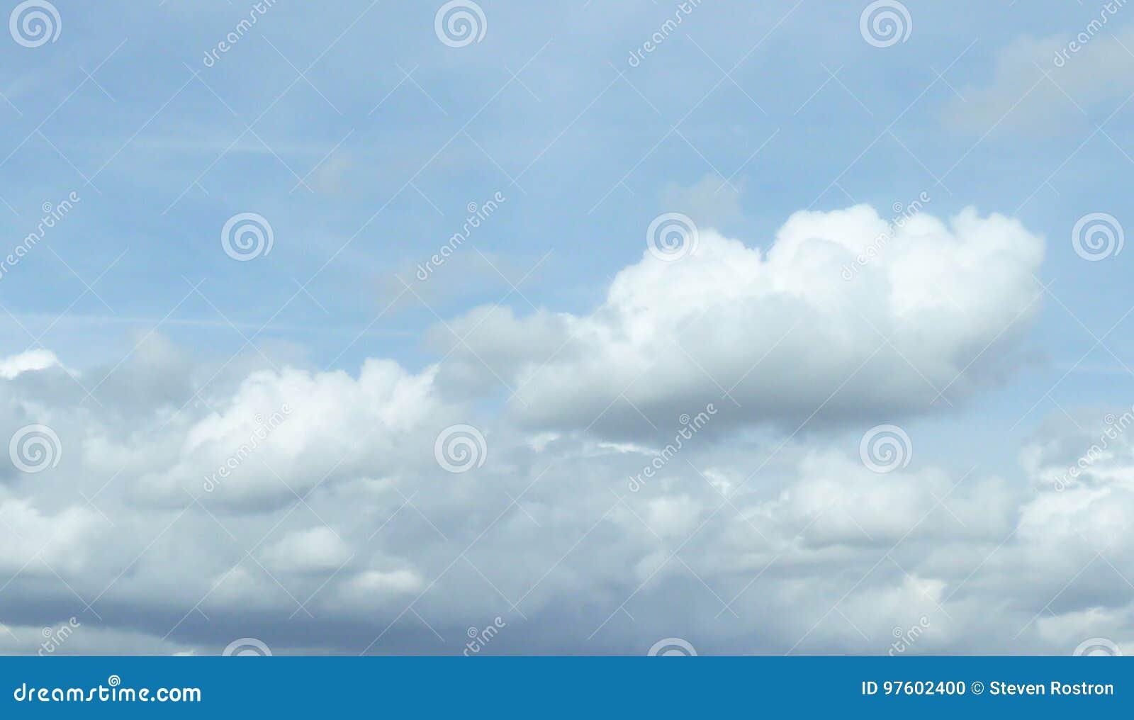 Weiße flaumige Wolken in Pale Blue Sky