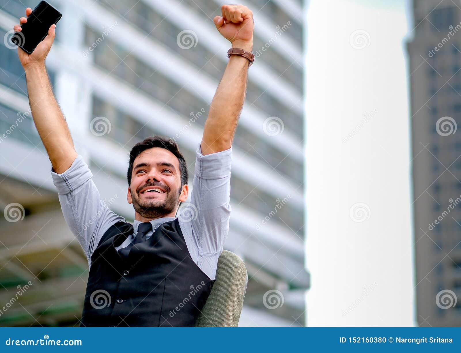Weiße Geschäftsmann-Showaktion von glücklichem und von erfolgreichem durch Hände oben mit auf Stuhl unter der Stadt zur Tageszeit