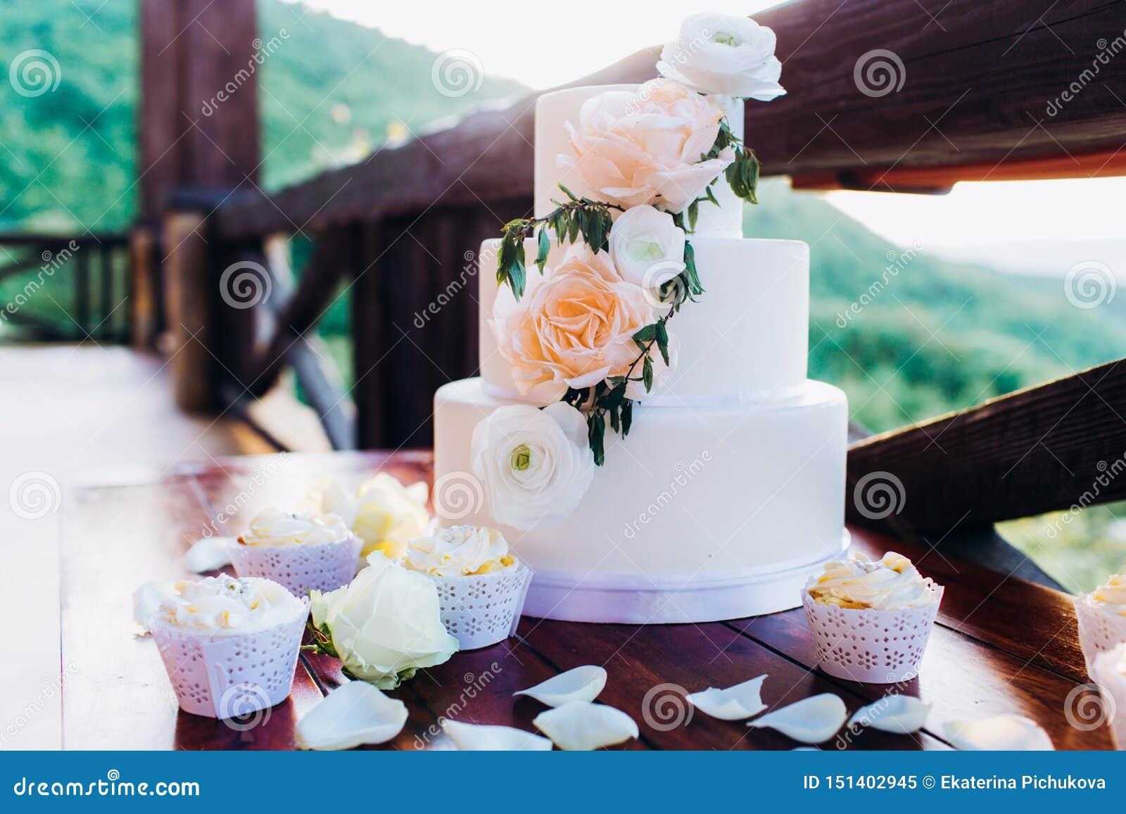 Weiße Hochzeitstorte mit Blumen auf einem Holztisch