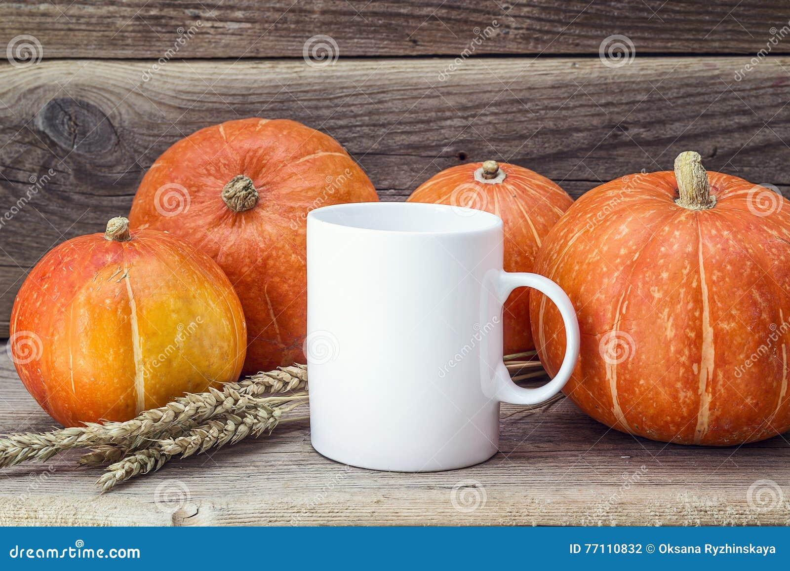 Weiße Kaffeetasse mit Kürbisen und den Ohren des Weizens auf dem alten Holz