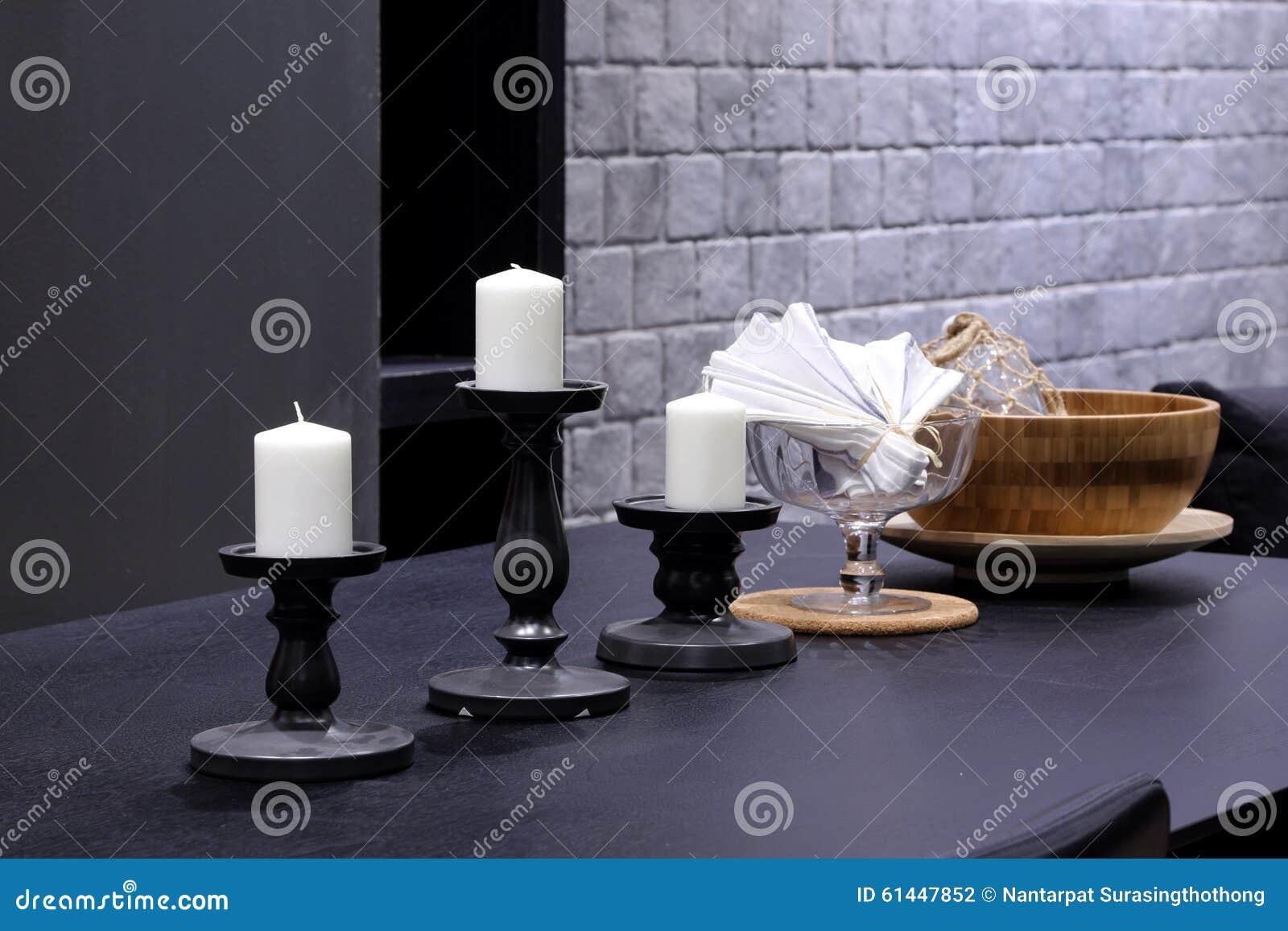 Weiße kerzen mit kerzenständer auf schwarzem holztisch in lebenr
