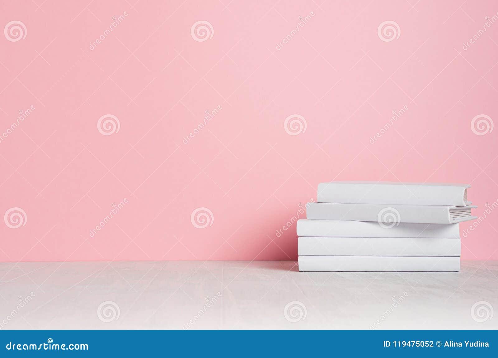 Weiße leere Bücher auf weißem Regal und weicher rosa Wand als modernem, elegantem Hauptdekor