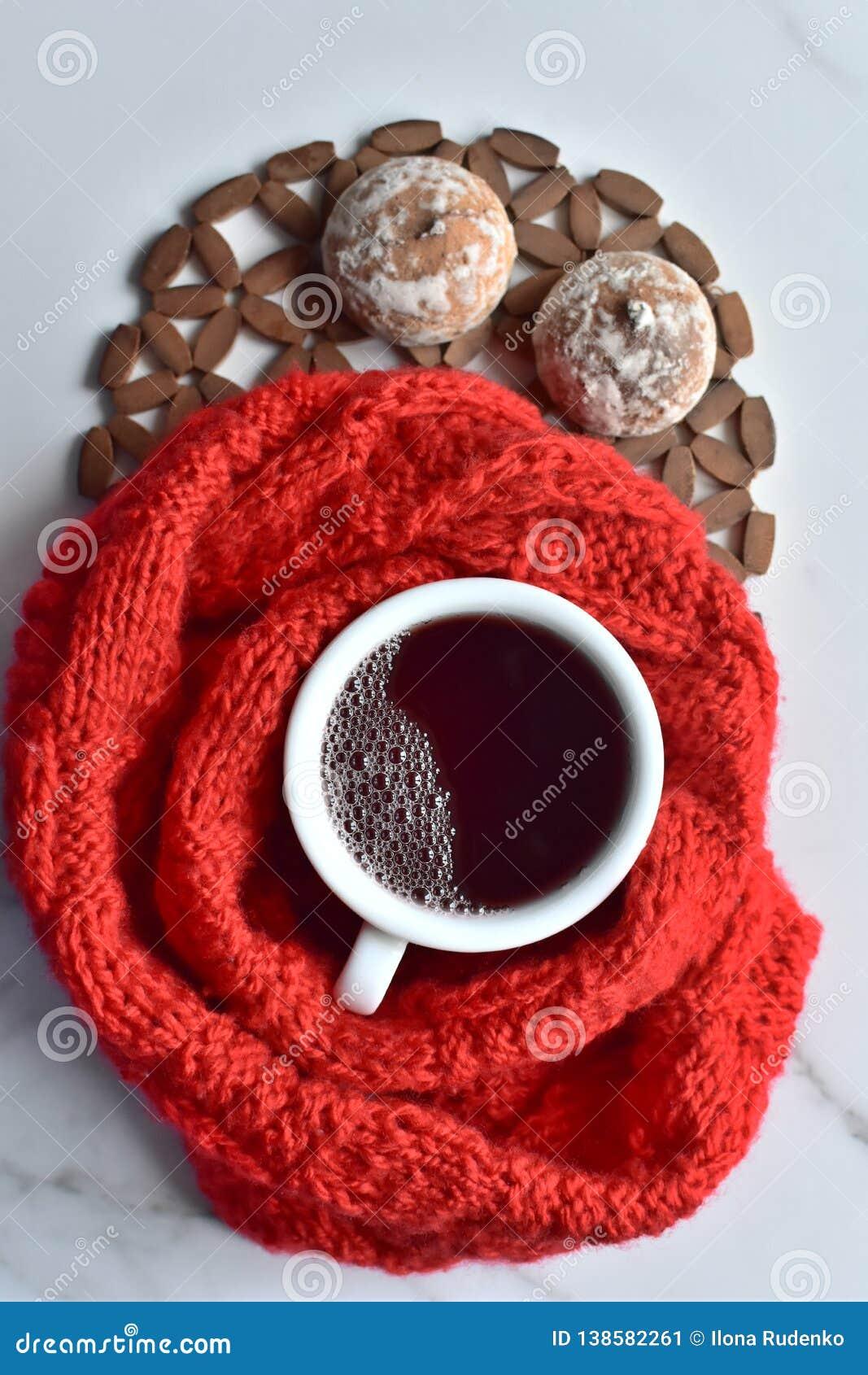 Weiße Schale heißer schwarzer Kaffee und süße Plätzchen mit dem roten gestrickten Stoff