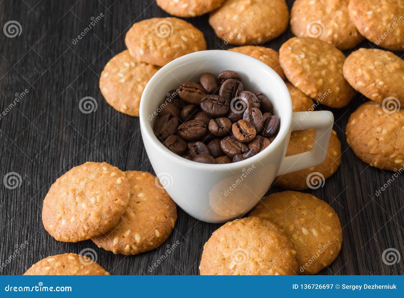 Weiße Schale mit Röstkaffeebohnen, Kekse mit Samen des indischen Sesams auf einem schwarzen Hintergrund
