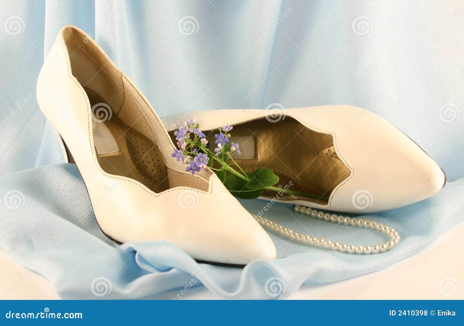 a9e3f4312c1ef6 Weiße Schuhe legen auf ein blaues Drapierung mit Korne und eine Blume