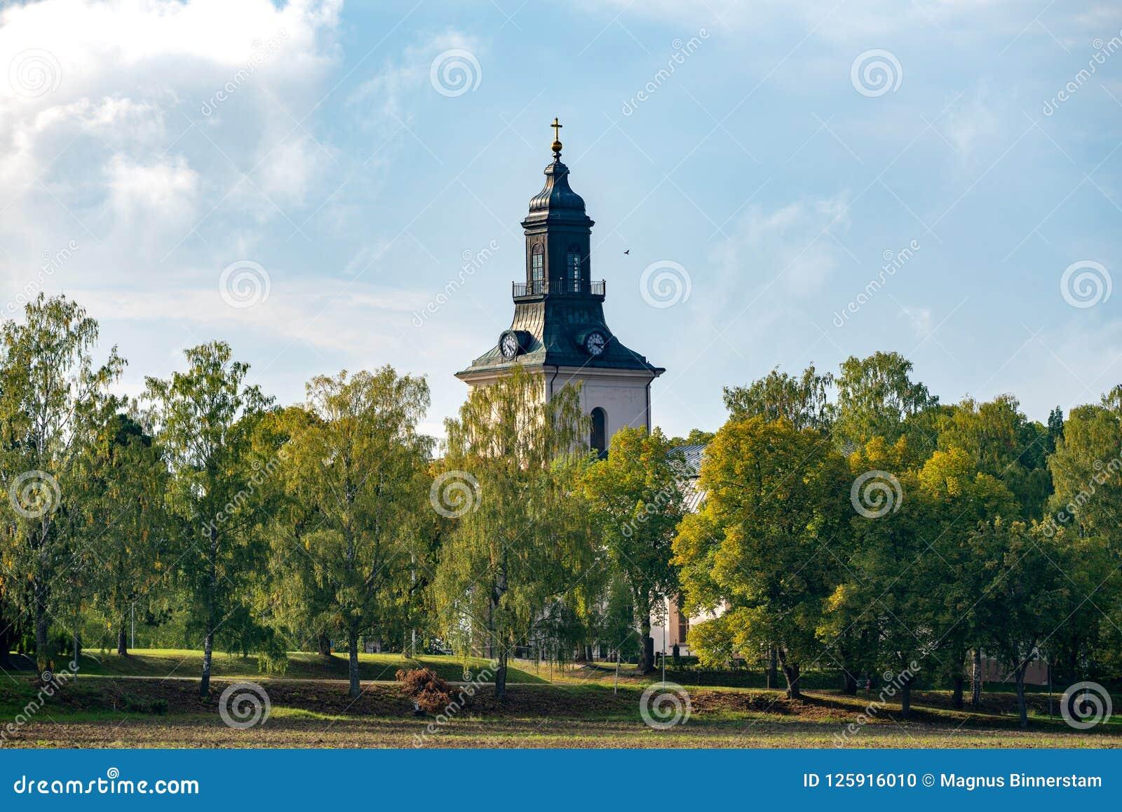 Weiße Steinkirche mit Herbst färbte umgebende Bäume