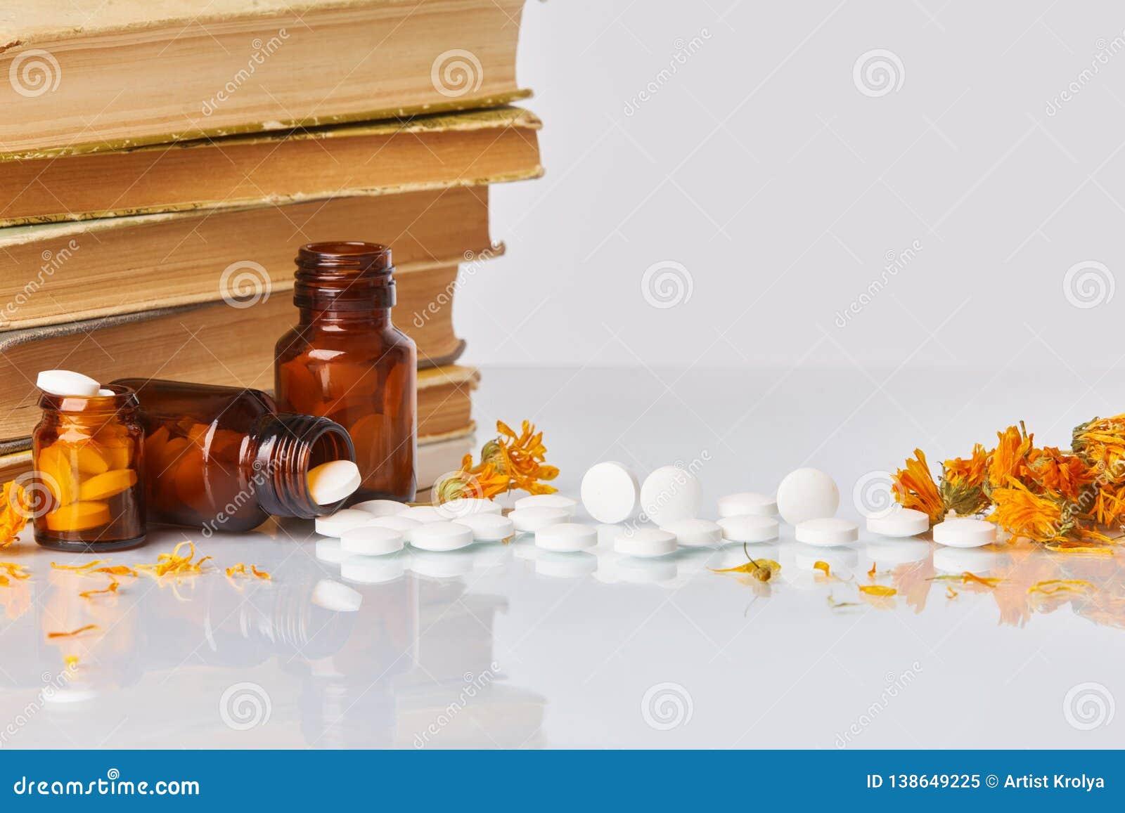 Weiße Tabletten und Pillen mit Ringelblume Calendula und alten Büchern auf weißem Spiegelhintergrund
