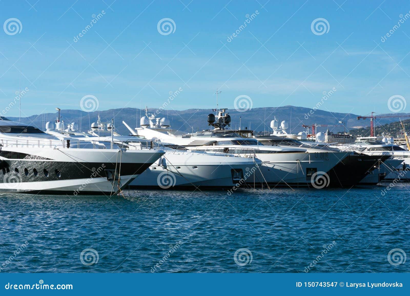 Weiße teure Yachten auf einem Hintergrund von Bergen an einem sonnigen Tag
