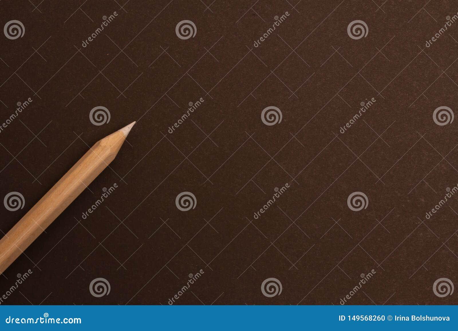 Wei?er Bleistift liegt diagonal auf einem schwarzen Hintergrund