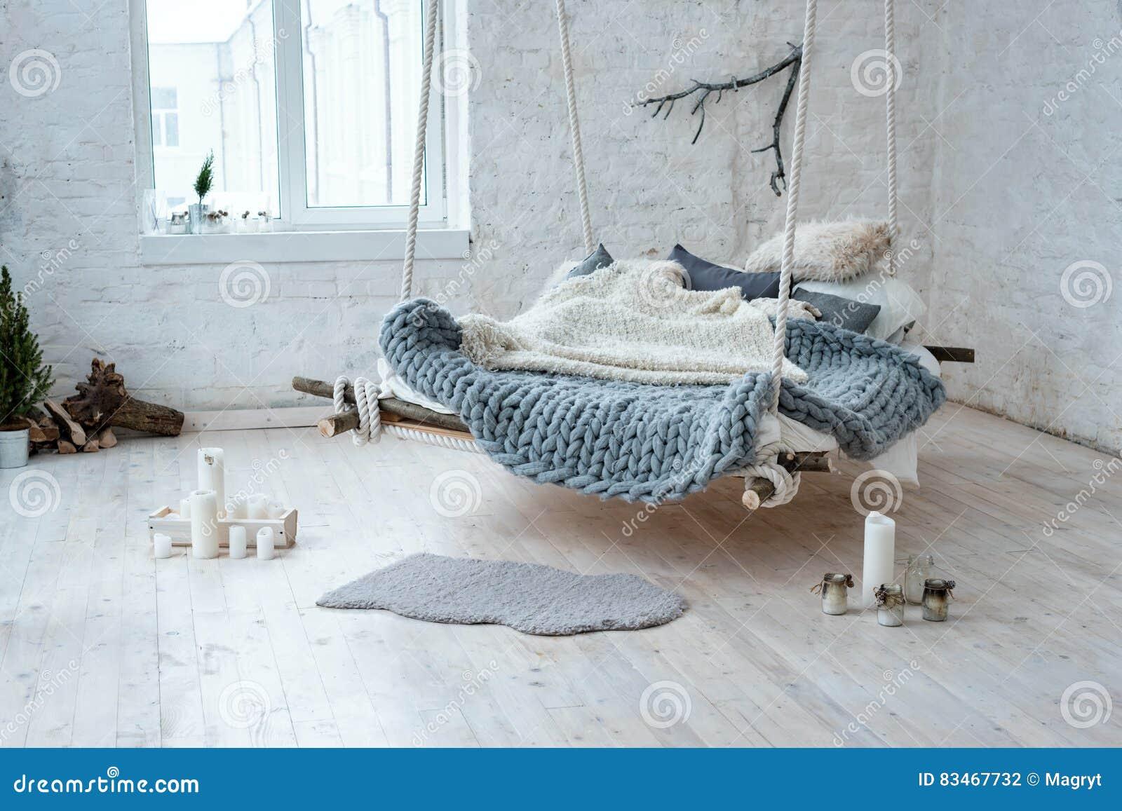 Weißer Dachbodeninnenraum in der klassischen skandinavischen Art Hängendes Bett verschoben von der Decke Gemütliches großes gefal
