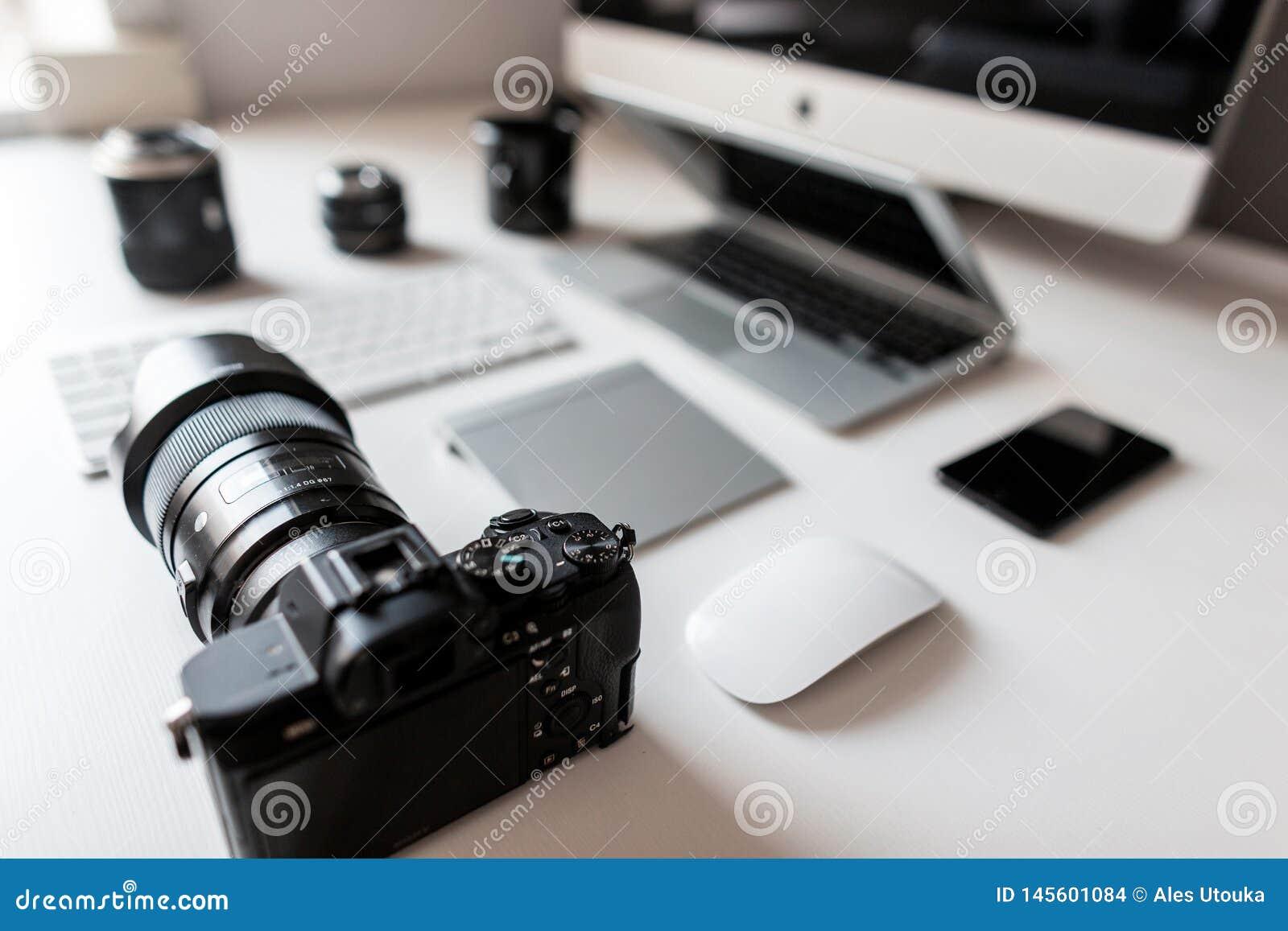 Weißer Desktop eines erfolgreichen Designers mit einem Laptop mit einer Maus mit einer modernen Berufskamera mit einer Tastatur m