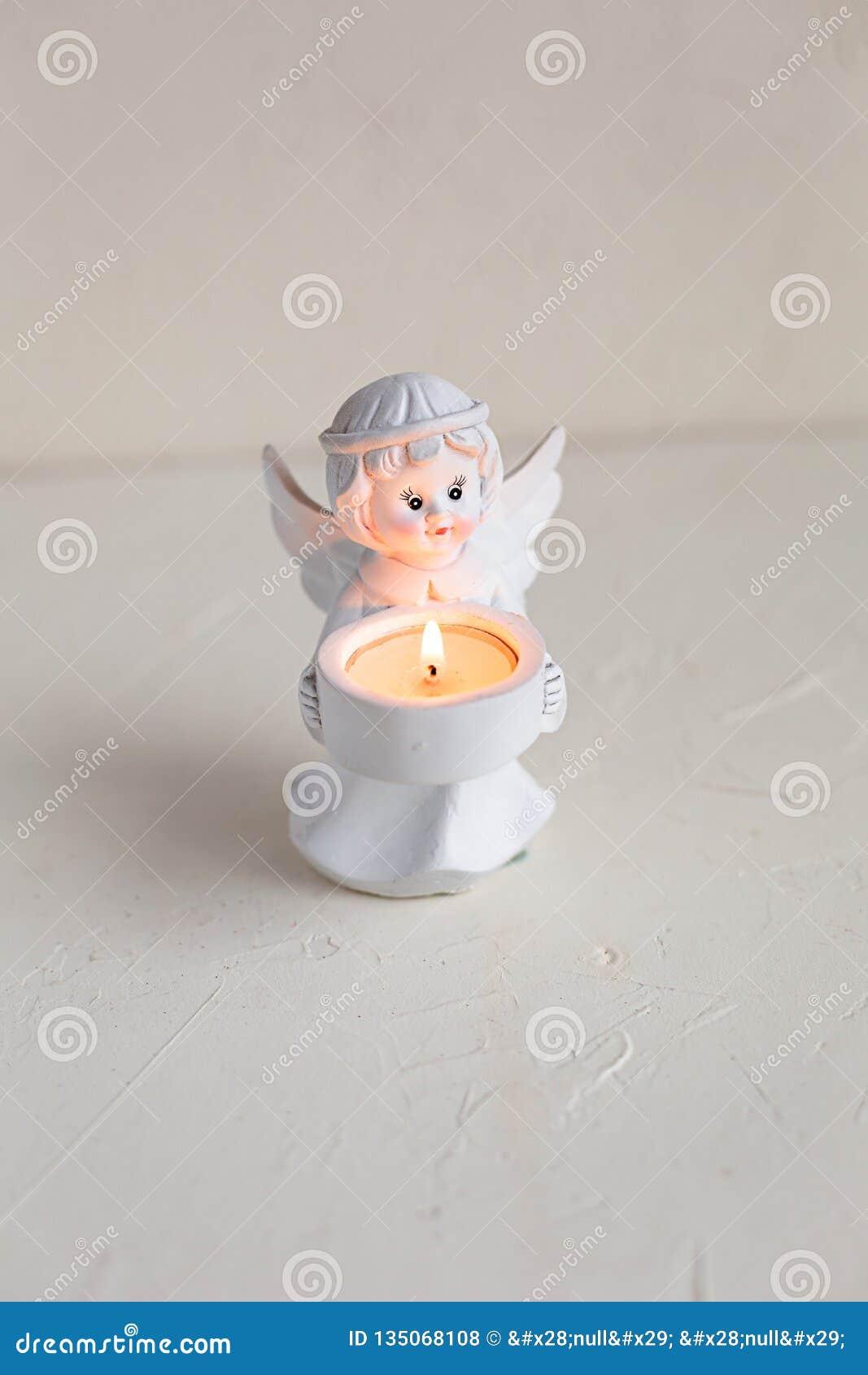 Weißer Engelskerzenhalter mit brennender Kerze auf Weiß