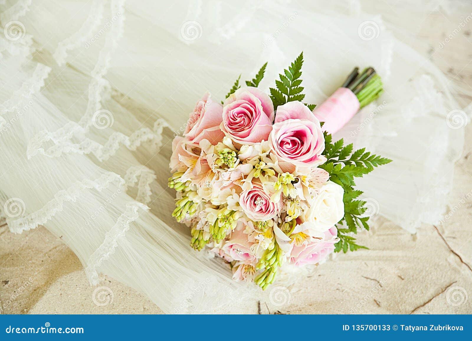 Weißer Sand, Hochzeitskleid und Blumenstrauß