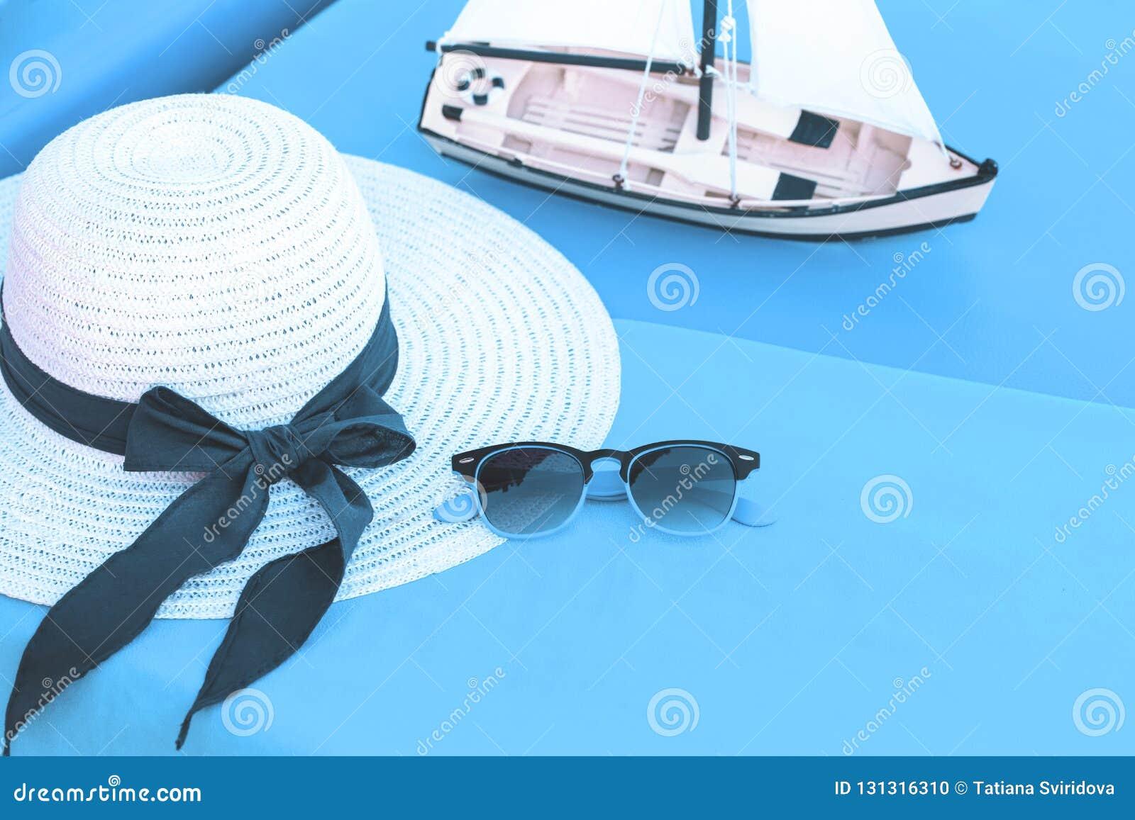 Weißer Sommerhut mit Sonnenbrille an der Küste