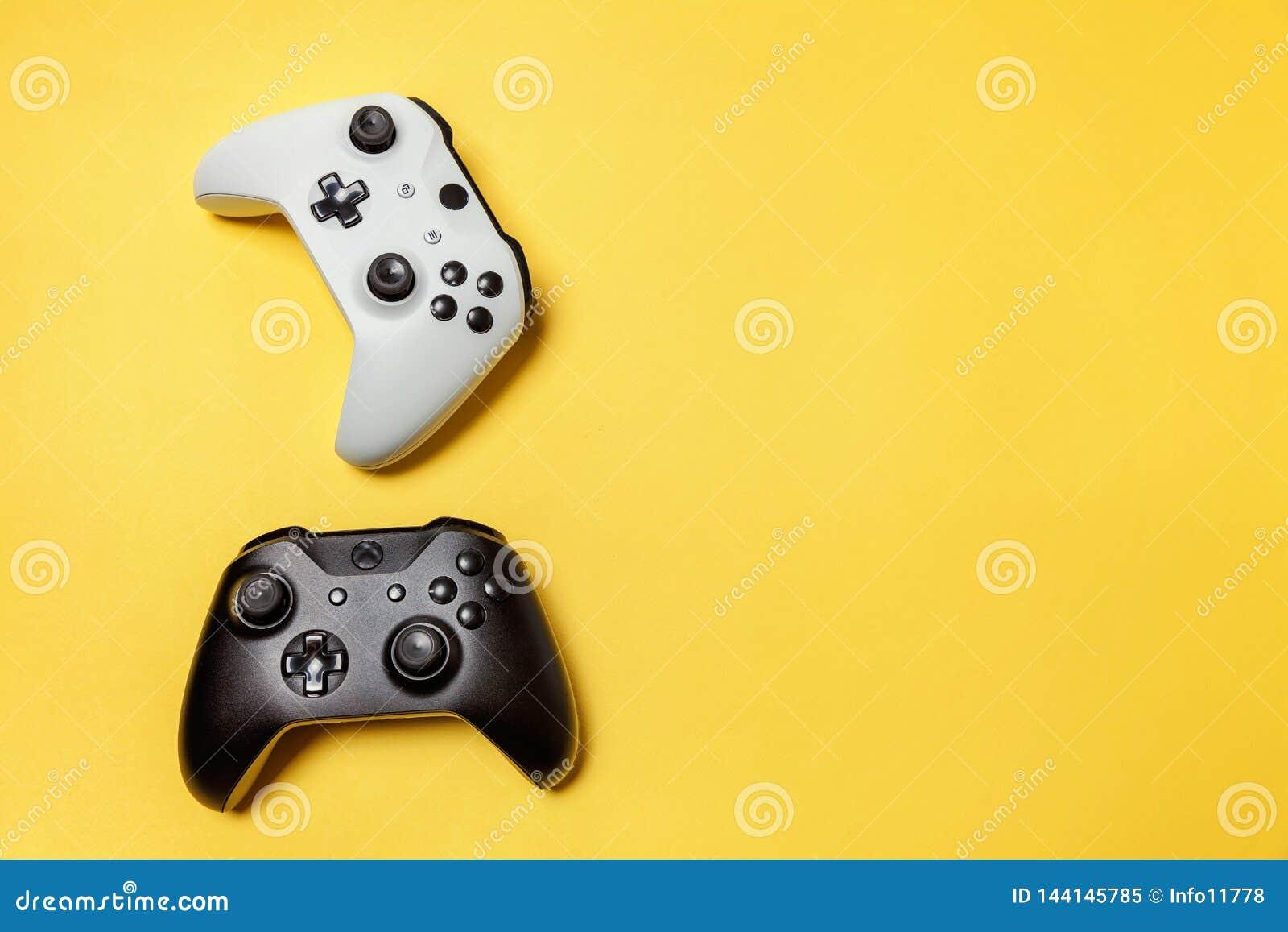 Weißer und schwarzer Steuerknüppel zwei auf gelbem Hintergrund Computerspielwettbewerbsvideospielsteuerkonfrontationskonzept