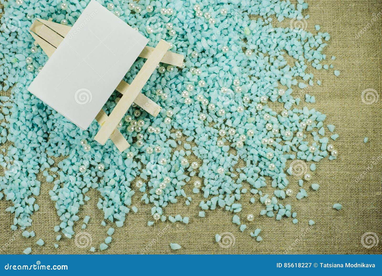 Weißes Gestell mit Weißbuch für Aufschriften auf dem zerfallenen blauen Kies