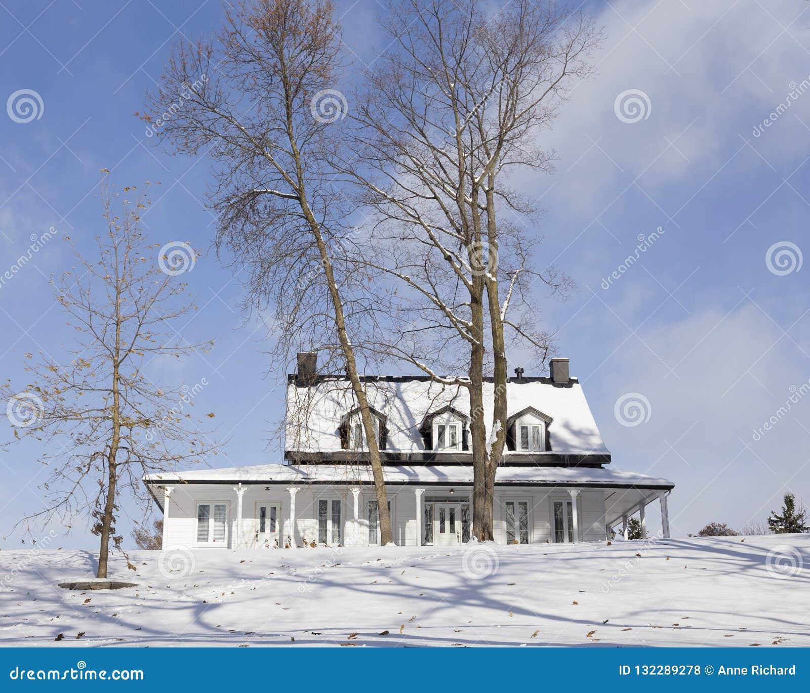 Weißes hölzernes Landhaus mit schneebedecktem schwarzem Dach in der Winterlandschaft