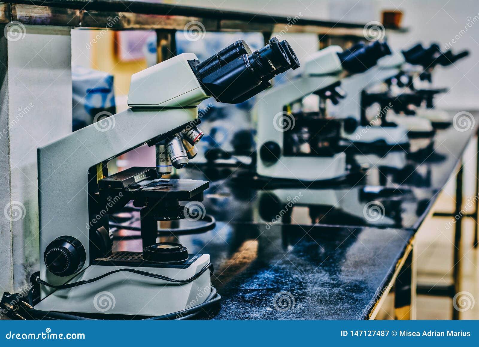 Weißes Mikroskop auf schwarze Tabelle