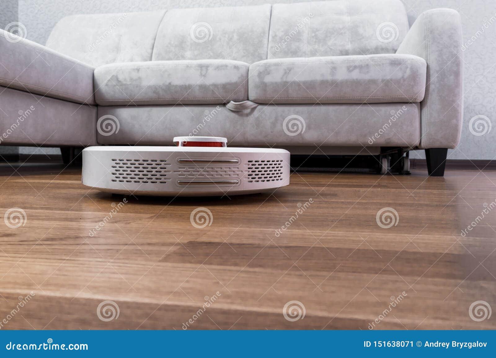 Weißes Roboterstaubsauger läuft auf der Laminatboden Nahaufnahme Der Roboter wird durch Sprachsteuerungen f?r direkte Reinigung g